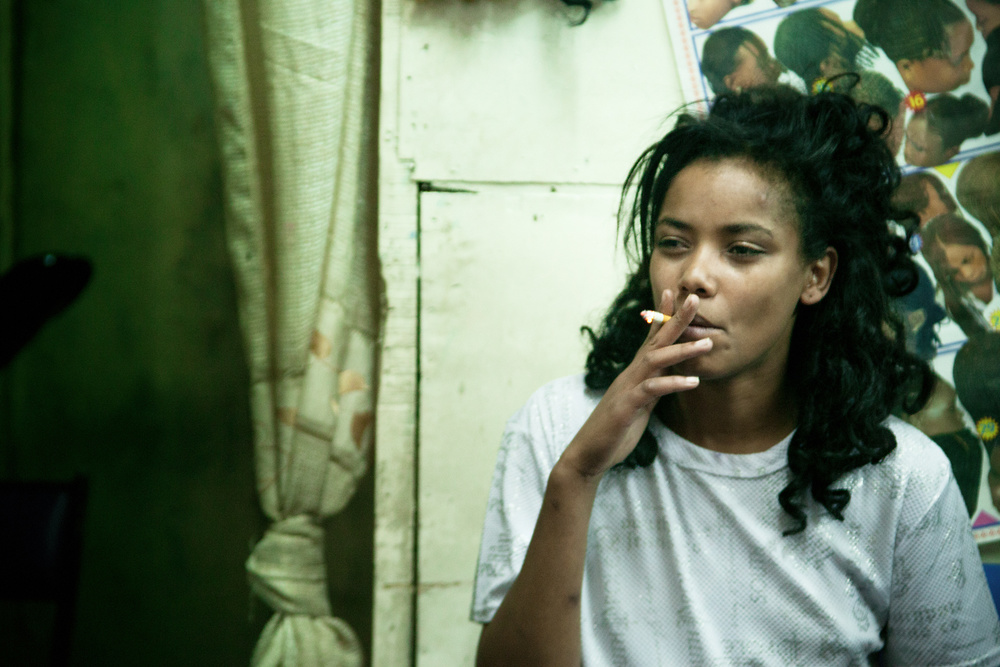 Mareya smoking. Her story is very sad. She moved to the capital when she was 14 and started working as a prostitute.Without her income the family can not survive, so she sends most of the money that she earns. The family thinks she is married to a rich man and keep demanding more and more money from her every month.