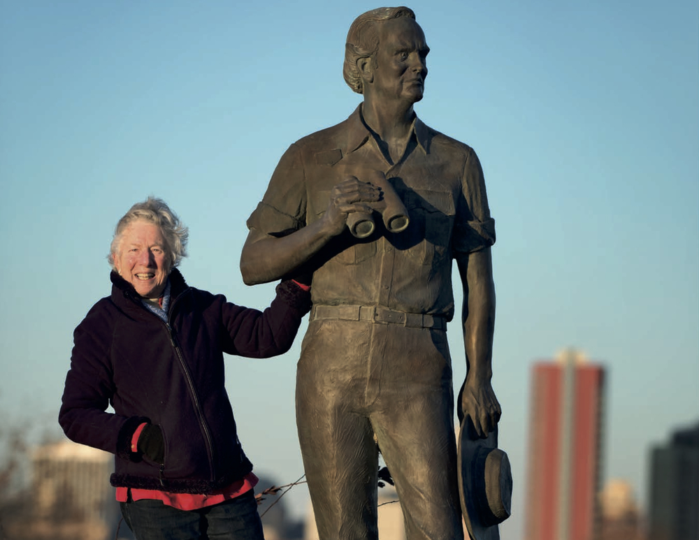 June Peterson standing with a statue of her husband, Governor Russell W. Peterson of Delaware, which was sculpted by Charles Parks.