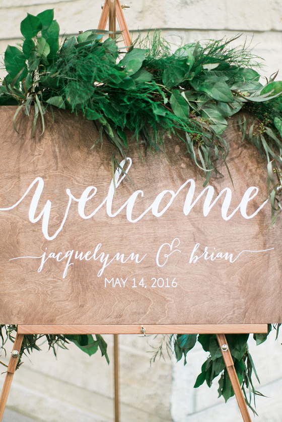 Elegant personalized welcome sign with draped greenery I www.avenueievents.com.png