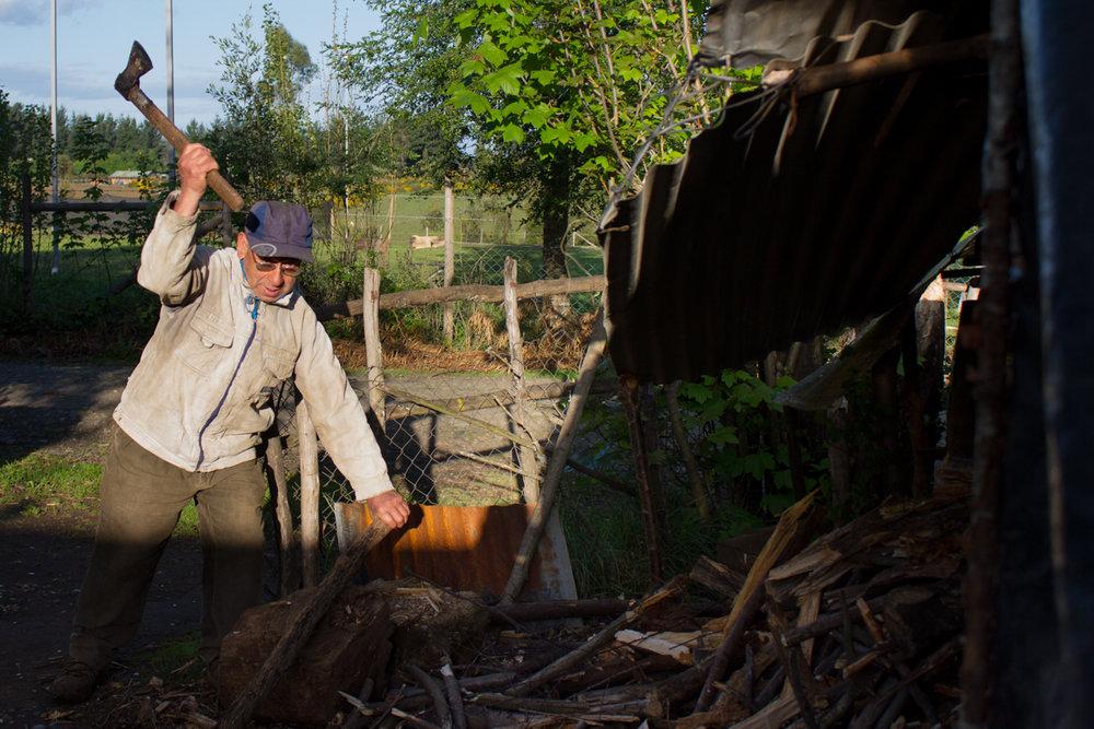 Samuel corta madera para calentar la casa. Tienen una estufa en dos partes de su casa que usan cada noche y durante el invierno.