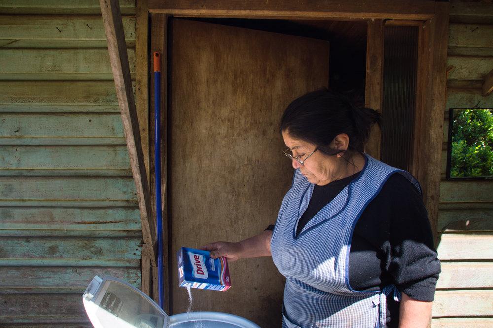 Norma usa una lavadora afuera de la puerta de la casa.