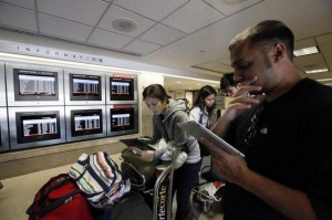 American Airlines passengers reading social media updates on delays.