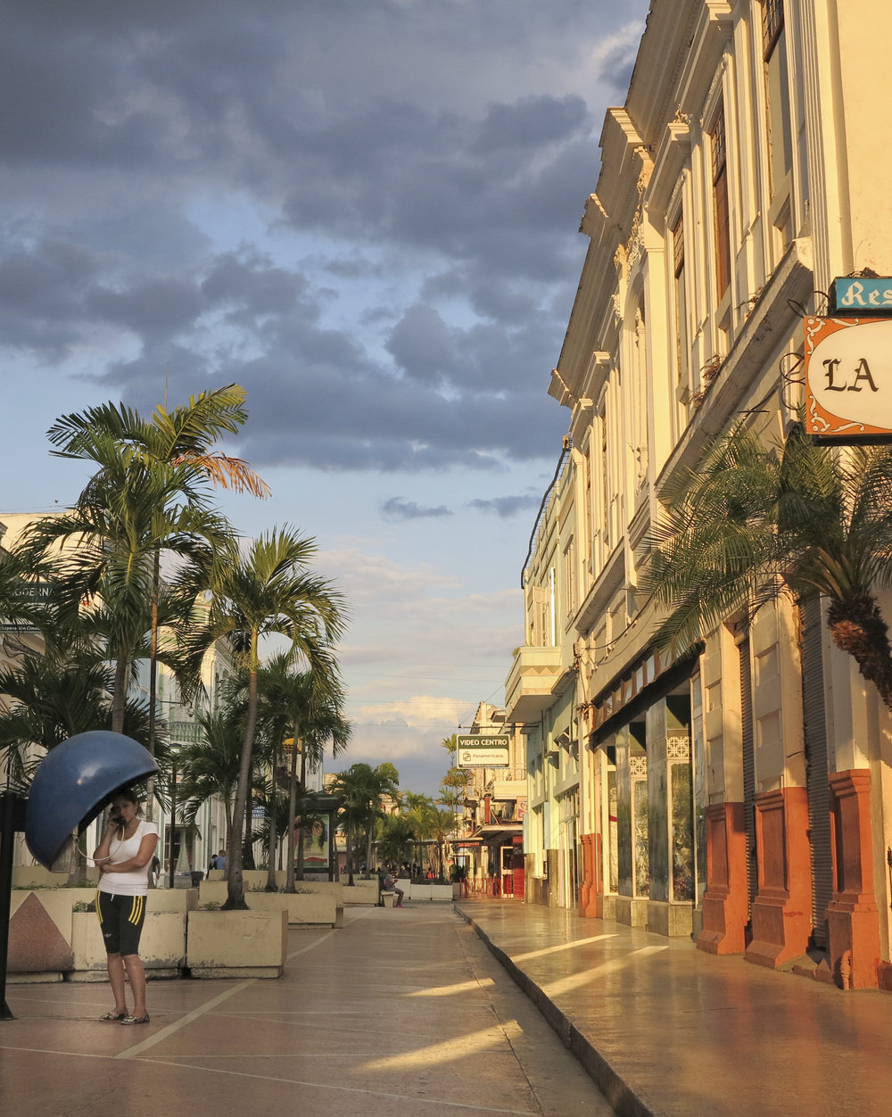 The pedestrian mall in the city of Cienfuegos Cuba. It's early evening after the shops have closed.