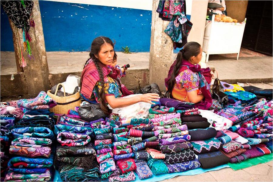"""Mujeres indígenas venden su artesanía en San Cristóbal de las Casas, en 2012. """"Las flores se emancipan definitivamente de su raíz gracias a la habilidad de las manos de las bordadoras."""" (p. 109)"""