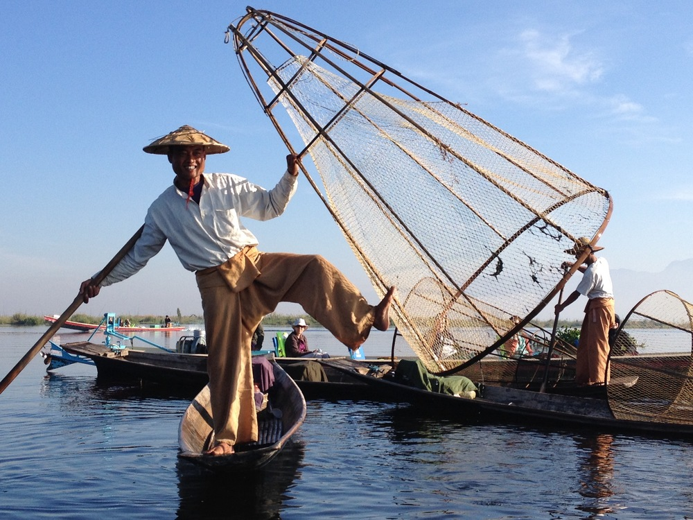A fisherman on Inle Lake demonstrates how they use three limbs at a time to maneuver their boat while trapping fish.