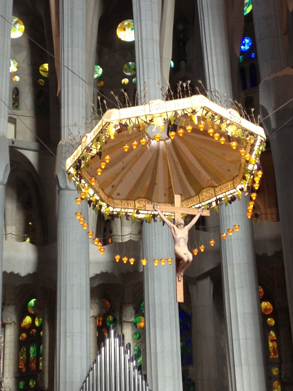 Inside Gaudi's trippy La Sagrada Familia with Jesus flying in on a grape covered parachute over the altar.