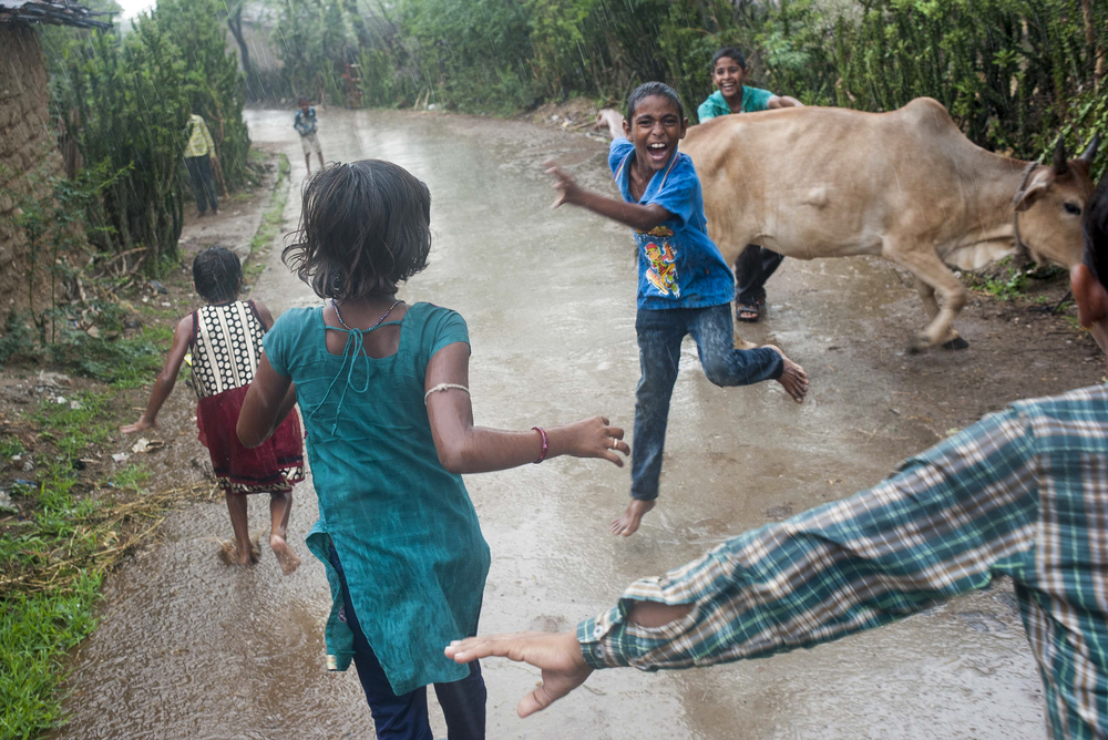 Children run through a rainstorm during monsoon season in Jeetawas, a small village outside of Railmagra in Rajasthan, India on July 21, 2015.