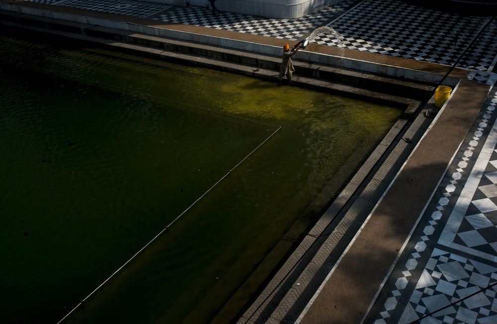 A worker removes water from the pool of the Gurudwara Baba Atal Sahib in the Golden Temple Complex in Amritsar, the major pilgrimage city for Sikhs from all over the world on July 29, 2015. The water is used in ritual bathing.