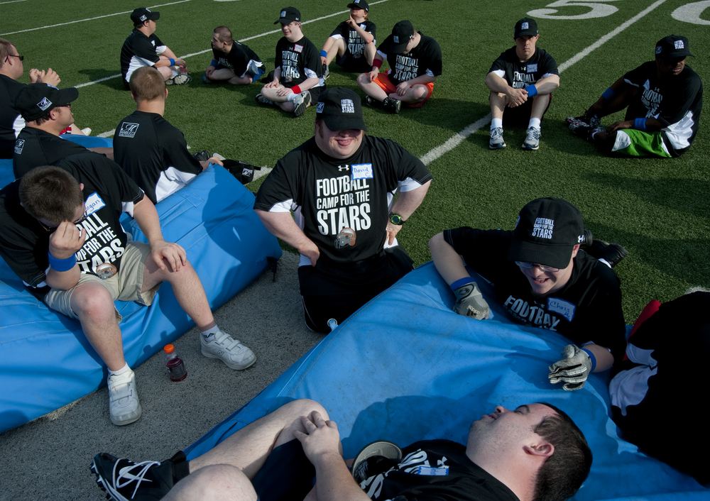 David Caliendo, middle, Chris McGough, right, and Anthony Curigliano, bottom, makes jokes together before the start of the Camp for the Stars practice, a football camp for people with Down Syndrome ages 15 to 30 that took place at the Woodland Hills High School stadium on Thursday, June 26, 2014.