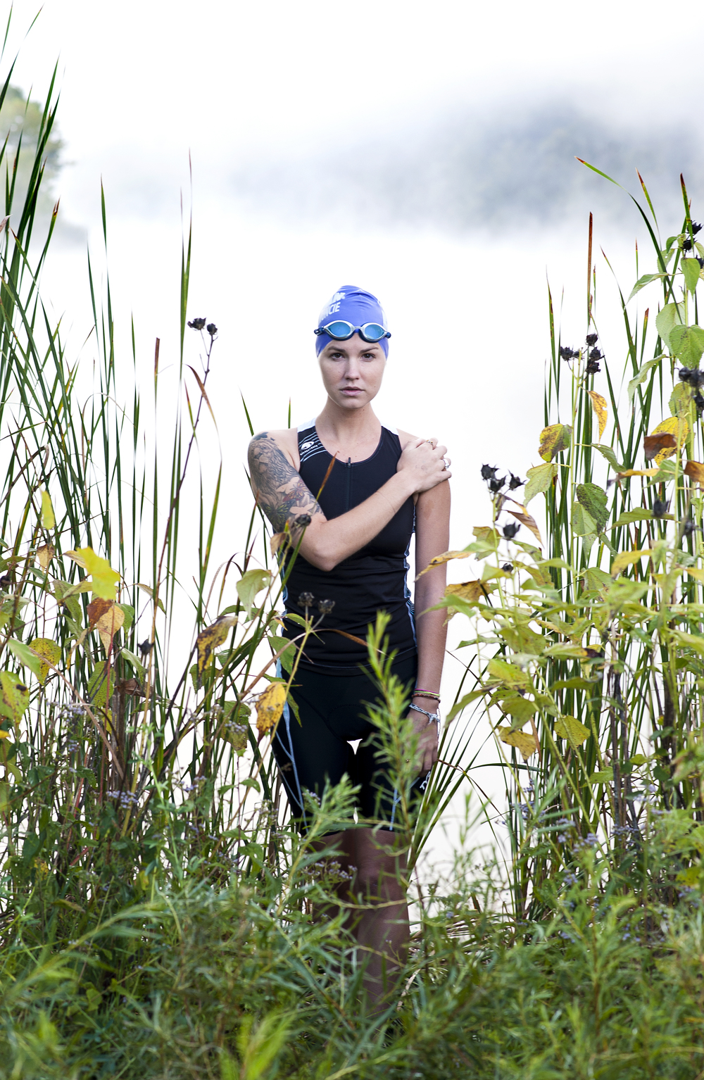 Triathlete Olivia Harlow poses for a portrait in the early morning fog of Strouds Run State Park where she regularly practices swimming in Athens, Ohio on September 15, 2015.