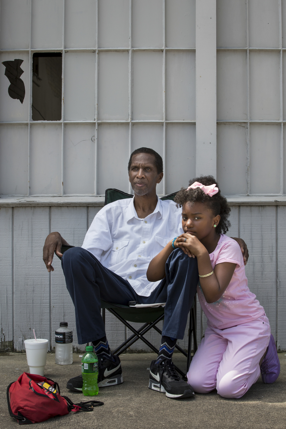 Donald Golightly and Jayla Hall, 9, wait along Broadway in Smoketown for the passing of Muhammad Ali's procession in his hometown of Louisville on June 10, 2016. Both are members of the Cable Baptist Church and came down with members of their congregation to witness the procession.