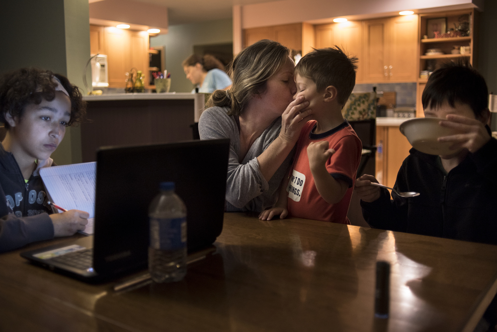 The Fuller family's mornings are hectic as each individual moves through their home to begin their day. DJ Fuller kisses her son Levi Fuller, 3, as Mya Fuller, 16, left, completes a lesson for her home schooling and Keaton Fuller, 12, right, finishes his bowl of cereal before heading to school.