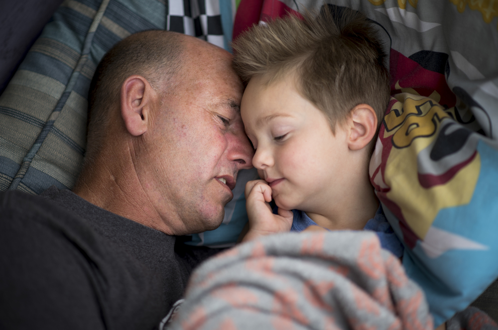 Lyle whispers to his adoptive son Levi to fall asleep as they take an afternoon nap together on their front porch.