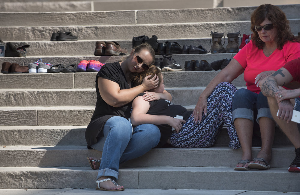 Lauri Martin, left, and Gale McComas, right comfort Abigale Boling, 11, on the State Capitol steps during the West Virginia Overdose Awareness Day Tribute in Charleston, WV on August 27, 2016. Abigale lost both of her parents to heroine overdoses and has lived with her grandmother Gale since she was three weeks old. Abigale's father Travis Boling passed away less than two months ago on July 7, and her mother Shana Weekly passed away a little over two years ago.