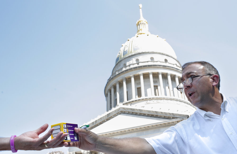 Dr. Michael Brumage of the Kanawha-Charleston Health Department distributes naloxone adminstration for free to a crowd of people at the West Virginia Overdose Awareness Day Tribute in Charleston, WV on August 27, 2016. The life-saving drug, while offered over-the-counter, is often too expensive to buy without a prescription.