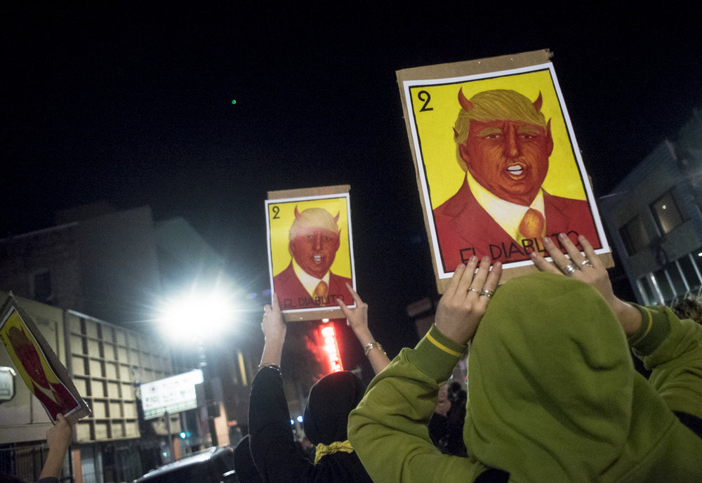 "Protesters hold up signs reading ""El Diablito"" (the little devil) during an anti-Trump protest in downtown Oakland on November 10, 2016."