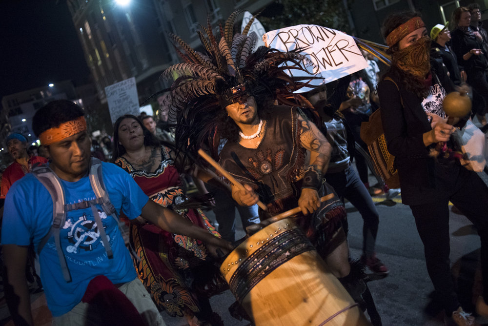 Performers dance and drum through the streets of downtown Oakland as part of the anti-Trump protest that took place on November 10, 2016.