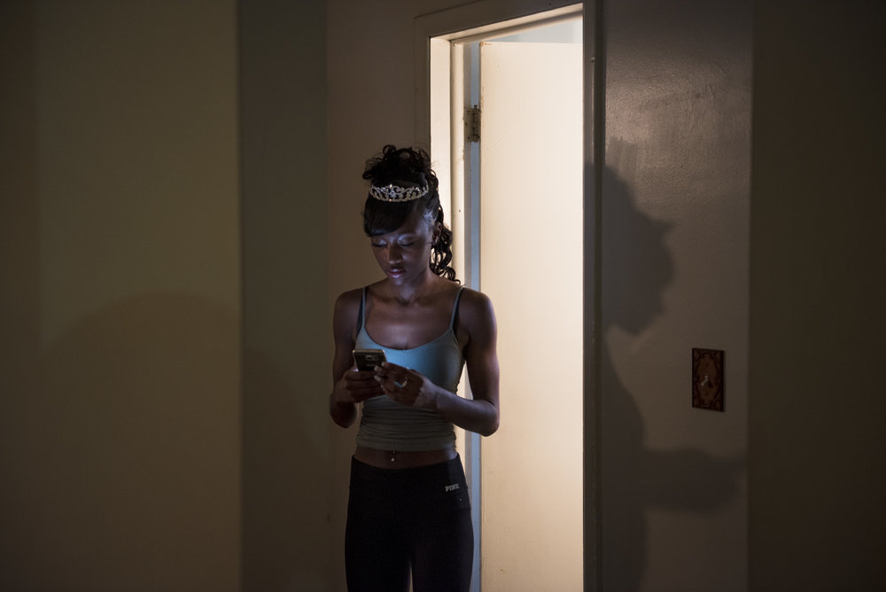 Linden-McKinley STEM Academy homecoming queen Michelle Burns texts her friends before getting ready for the homecoming dance at her home in Columbus, Ohio on Friday, October 16, 2015.