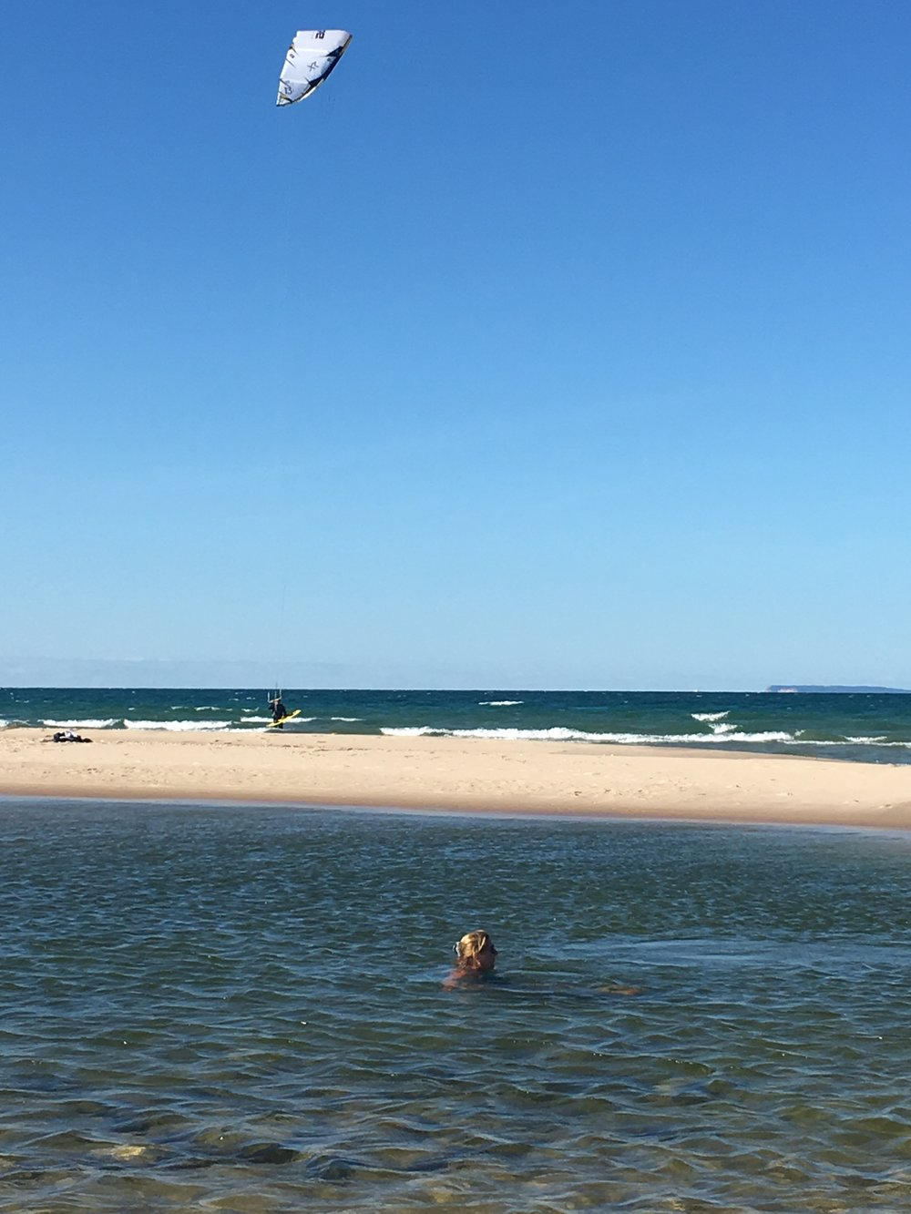 Jani in the mouth of the Platte river with a windsurfer on Lake Michigan.