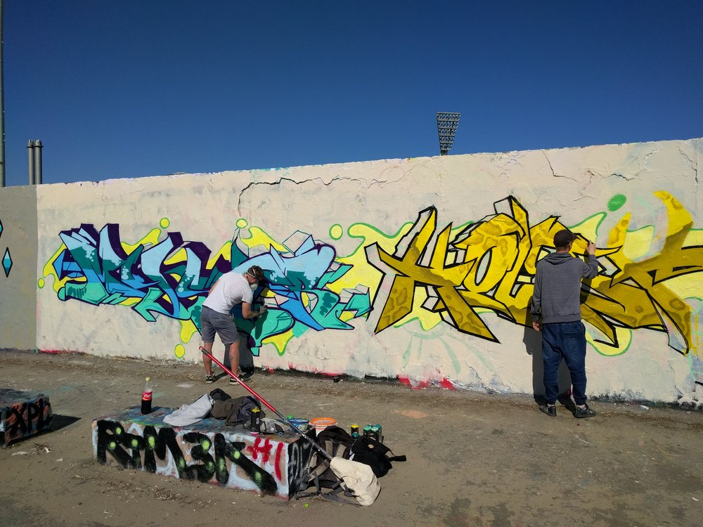 A long wall of graffiti artists working on their art above the park