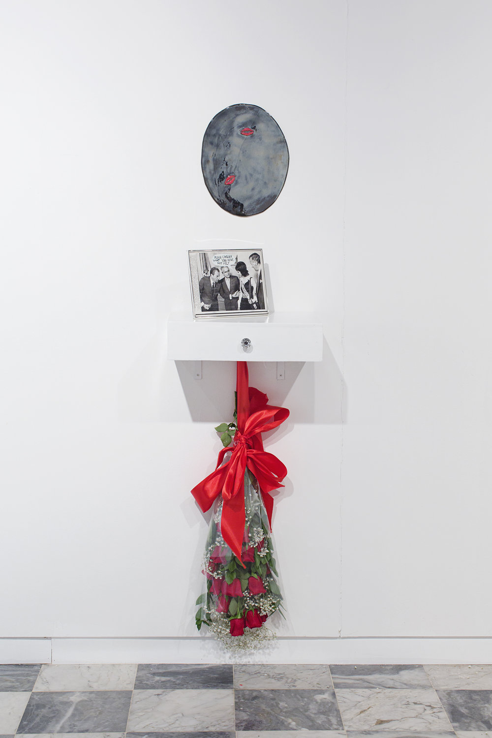 "Marisol Malaret, Miss Universe 1970, 2018   Porcelain mirror, original 1970 press photo on vanity, red roses, silk, cellophane, baby's breath, hardware Porcelain mirror 14 x 8"" (35.6 x 20.3 cm), vanity shelf 12 x 18 x 4.5"" (30.5 x 45.7 x 11.4 cm)  Overall dimensions variable"