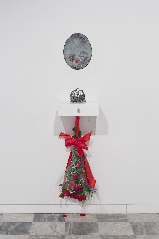 "Deborah Carthy-Deu, Miss Universe 1985, 2018  Porcelain mirror, porcelain crown, vanity, red roses, silk, cellophane, baby's breath, hardware Porcelain mirror 14 x 8"" (35.6 x 20.3 cm), vanity shelf 12 x 15 x 4.5"" (30.5 x 38 x 11.4 cm)   Overall dimensions variable"