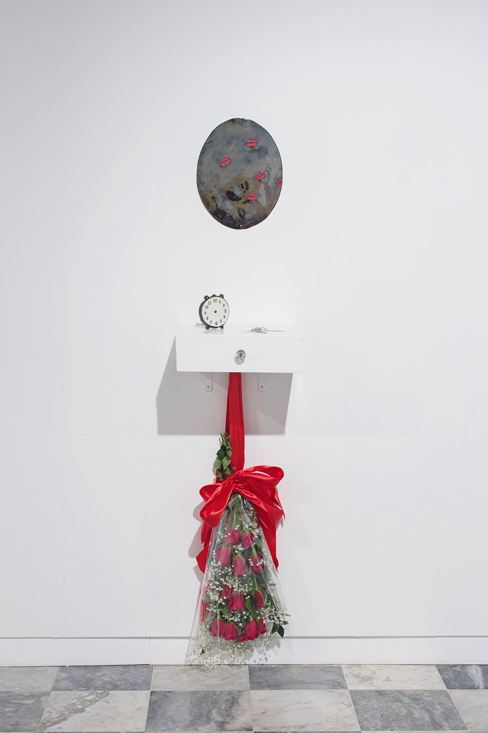 """Denise Quiñones, Miss Universe 2001, 2018   Porcelain mirror, porcelain clock without hands, mother of pearl, red abalone, black mother of pearl carved keys on vanity, red roses, silk, cellophane, baby's breath, hardware Porcelain mirror 14 x 8"""" (35.6 x 20.3 cm), vanity shelf 12 x 15 x 4.5"""" (30.5 x 38 x 11.4 cm)  Overall dimensions variable"""