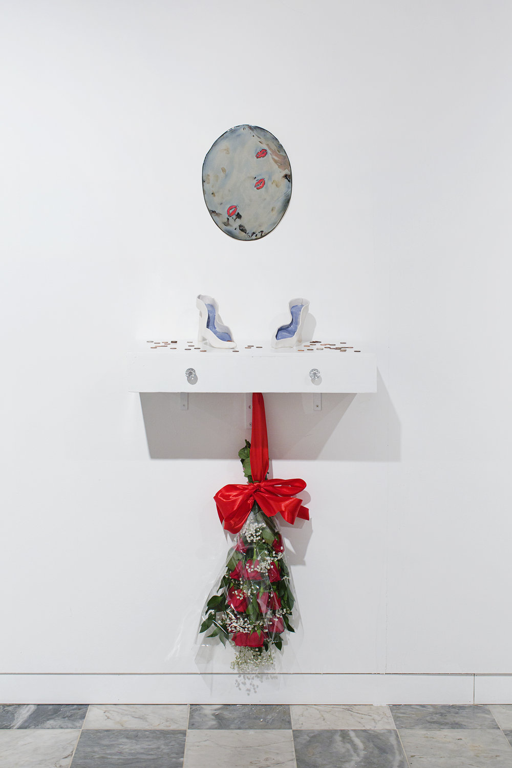 """Zuleyka Rivera, Miss Universe 2006, 2018   Porcelain mirror, porcelain wishing well shoes on vanity, pennies, nickels, dimes, red roses, silk, cellophane, baby's breath, hardware Porcelain mirror 14 x 8"""" (35.6 x 20.3 cm), vanity shelf 12 x 28 x 4.5"""" (30.5 x 71.1 x 11.4   cm) Overall dimensions variable"""