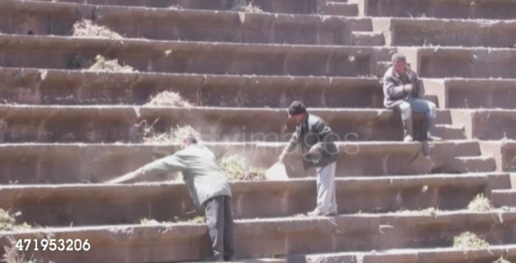 A scene from the video release by Bosra al-Sham's local council showing residents cleaning the steps of the ancient amphitheater as part of the restoration process.
