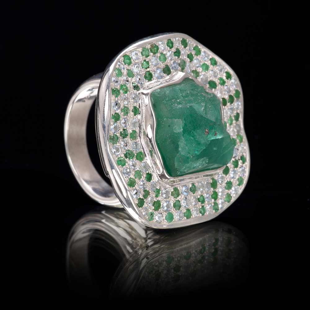 A rough emerald from Colombia is encircled by a wave of aquamarine and emerald pavé. Ring is set in 925 silver