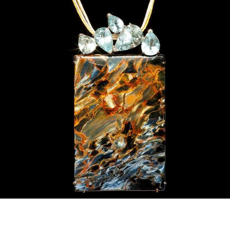 A large rectangular pendant (5 cm x 4 cm) of blue pietersite (Namibia) capped by 5 faceted aquamarines (Madagascar), set in 18k white gold