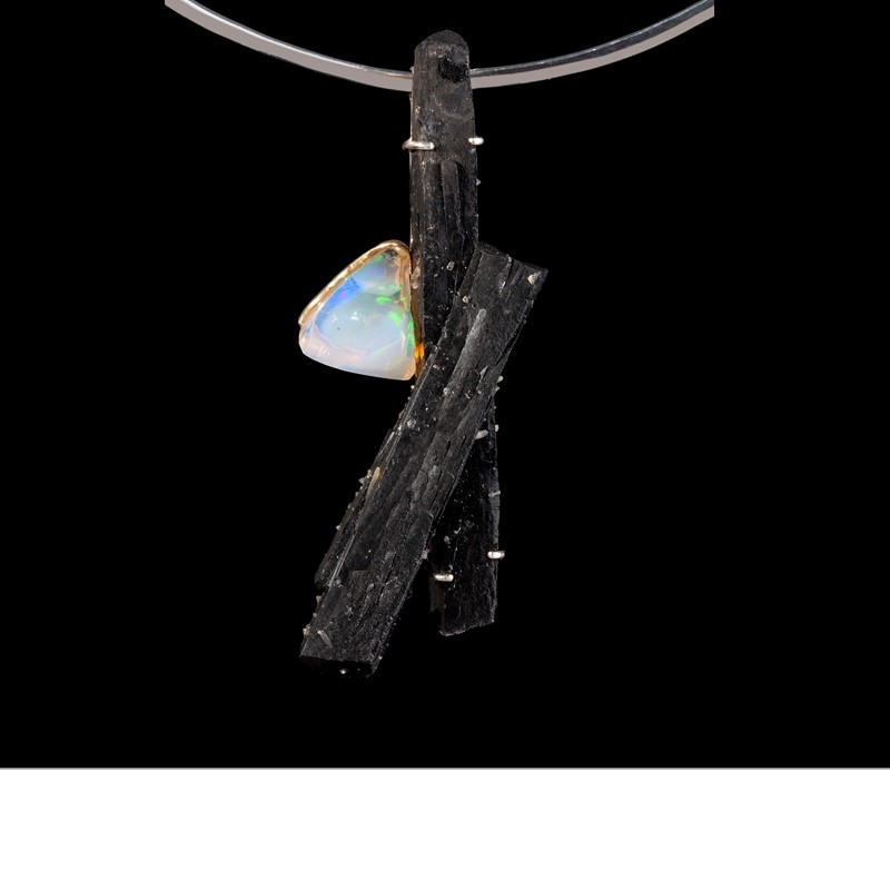 A double schist, hexagonal crystal form, is a stark contrast to a luminescent Wallo (Ethiopia) opal clinging to its side. Set in 925 silver and suspended from a silver choker