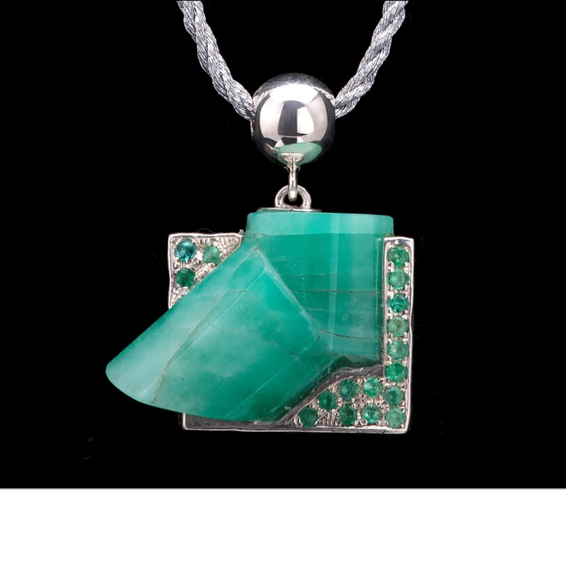 A macle or unique double rough emerald crystals are embraced by aquamarine and emerald pavé. Pendant is set in 925 silver