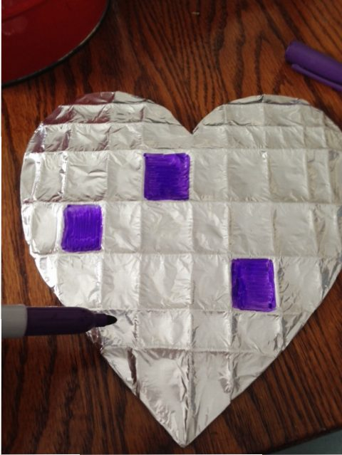 Using Sharpie markers to gently color in the squares so as not to tear the foil.