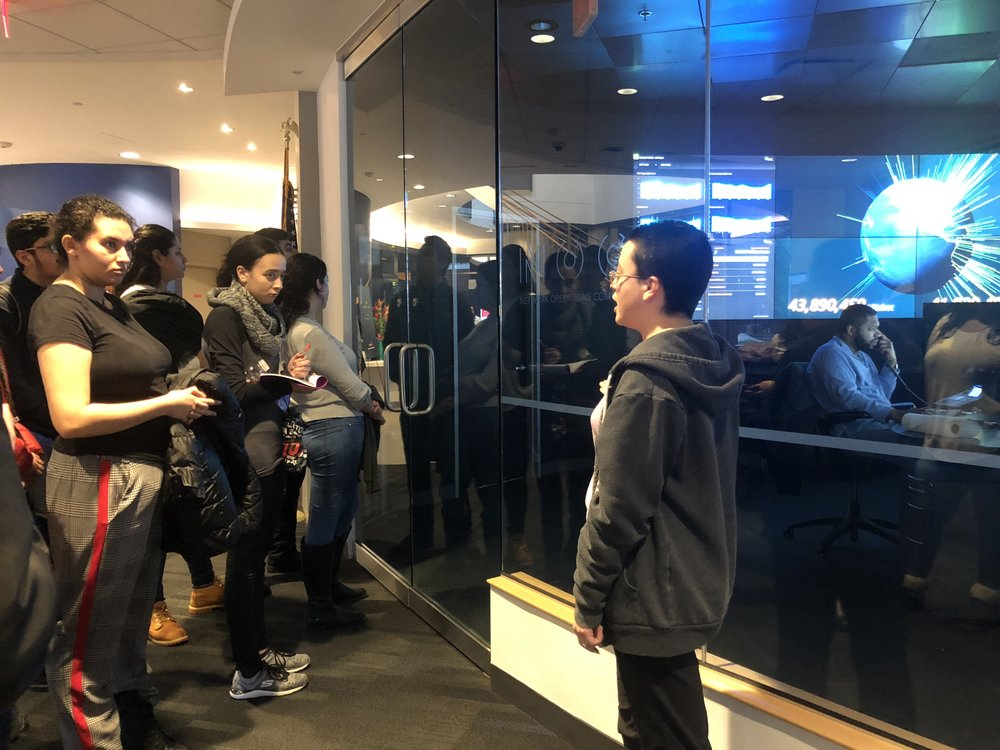 Students listen and take notes as they toured Akamai's building and spoke with Akamai employees.