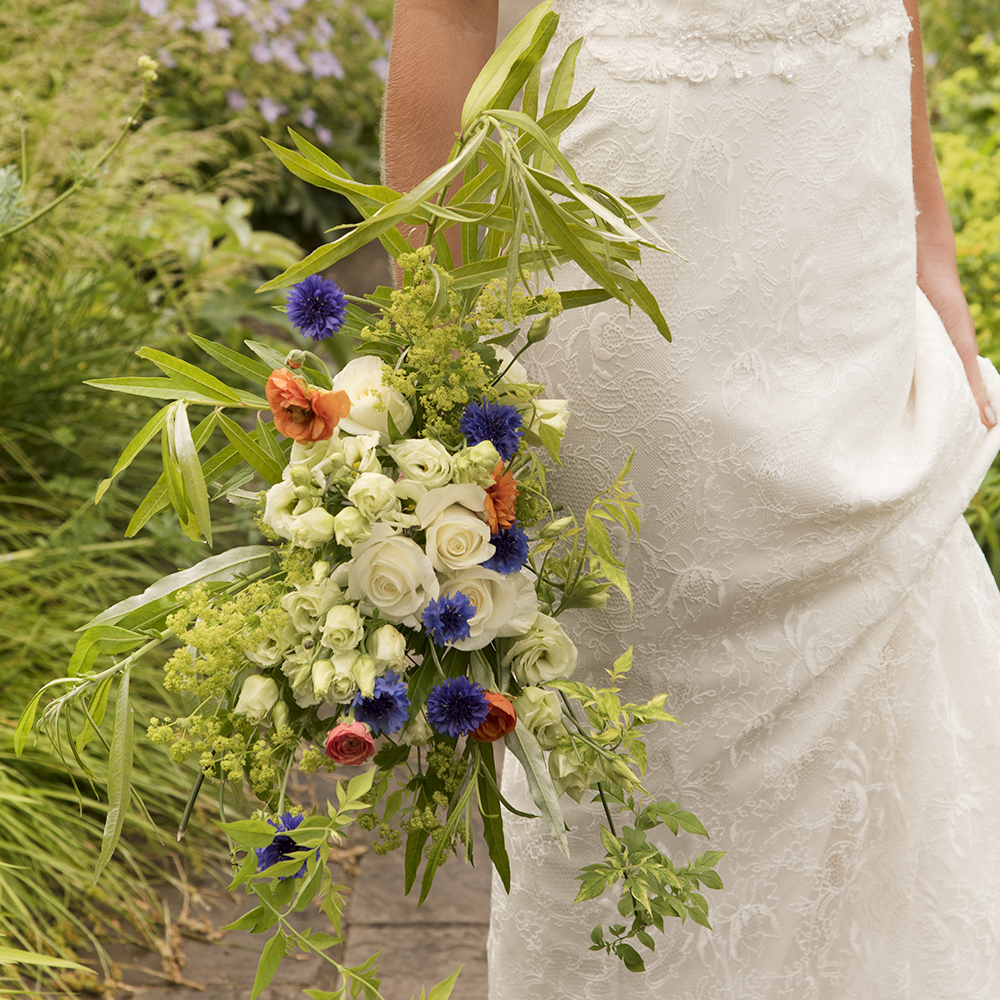 Natural bridal bouquet with red, white and blue flowers