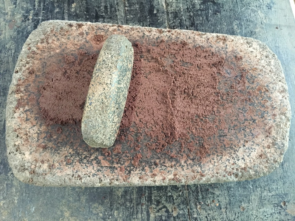 Using an ancient indigenous grinding stone to turn the beans into a paste