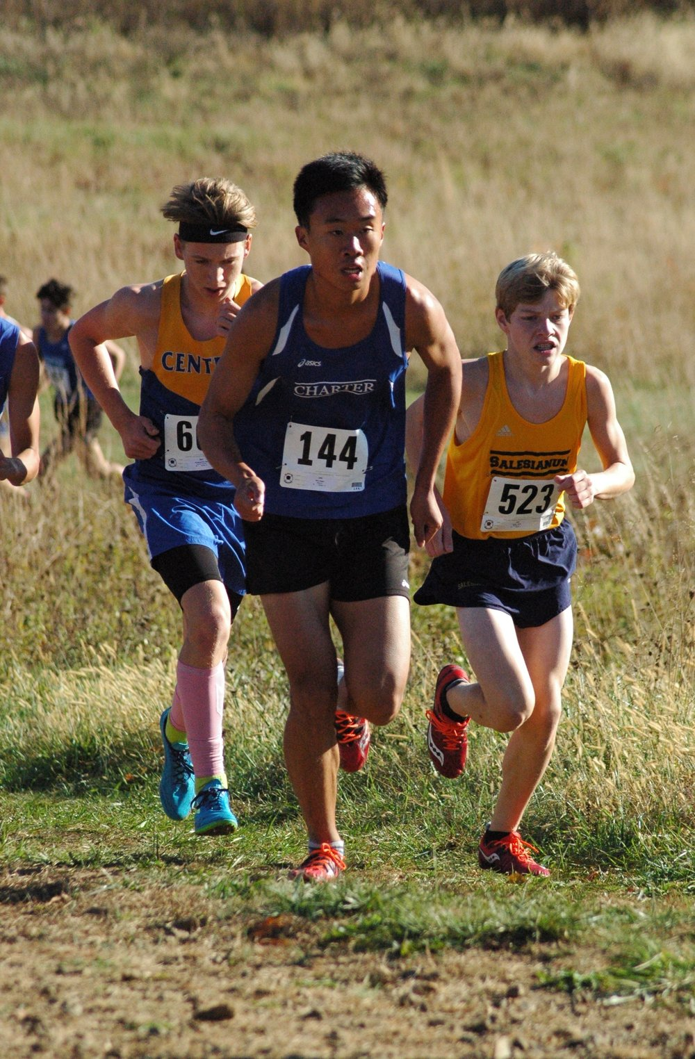 Senior Logan Kim (in Charter uniform) charges up the dreaded Maintenance Hill with ease, passing a few runners along the way.  Photo by Joe Hackman  .