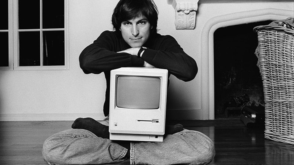 Picture of a young Steve Jobs with the Macintosh on his lap. Source is The Verge Website.