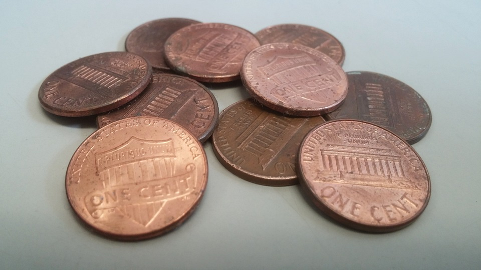 Change such as the pennies pictured above are not only a time-wasting nuisance but impose a serious cost on the economy. Estimates approach 100 million dollars lost annually to these hefty slices of metal. Photo from pixabay.com.