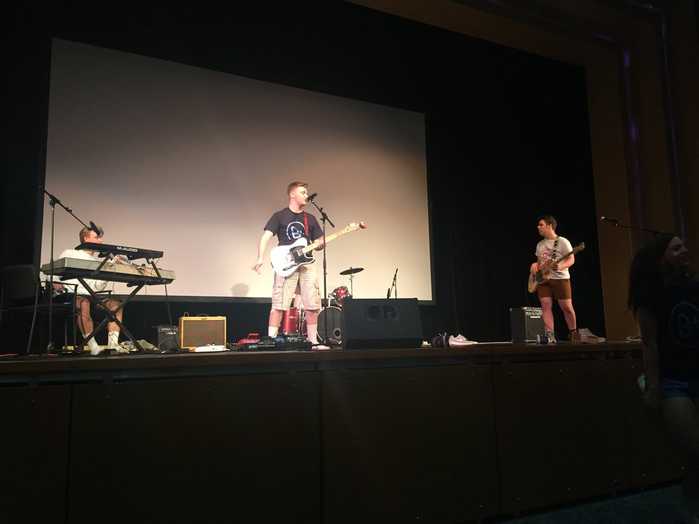 Shooting Shark, a rock band composed of Charter students Ethan Andress (left), Nate Lamborn (center), Evan Kipp (behind Lamborn), and Brian Johansson (right) performing in the Cab Calloway theater at CHVRTERTHON. Photo by Grady McPeak
