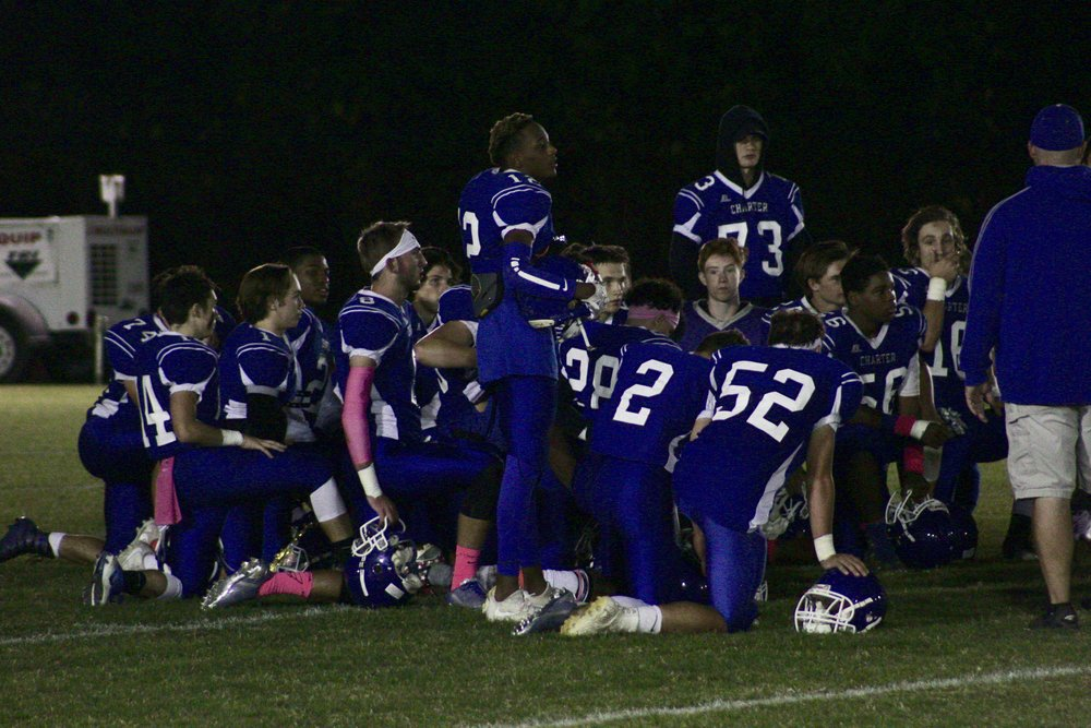 The Charter Force football team huddles up briefly during their annual homecoming game, played for the first time Firday night under the lights. Record numbers of attendees witnessed a 41-0 win against First State Military Academy. Photo by Natalie Smith.