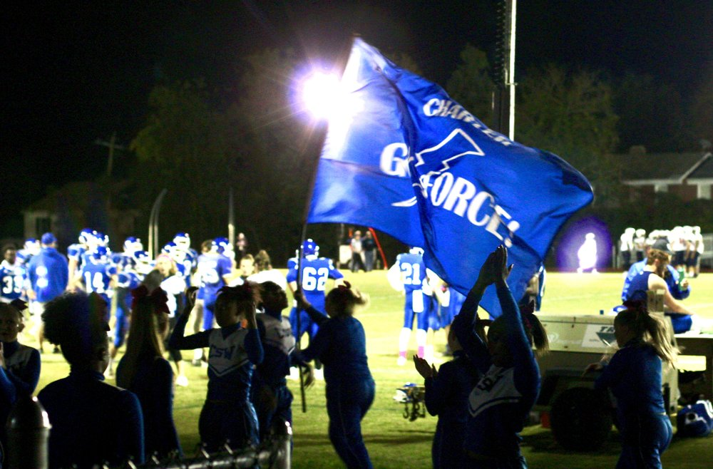 "The Charter Cheer Team leads the crowd through a routine and brandishes a ""Go Force!"" banner. The lights, rented to host the nighttime game in CSW's own stadium appear in the background. Photo by Natalie Smith."