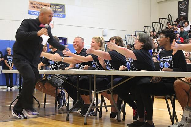 Mr. Anderson, as Steve Harvey, gives high-fives to the teachers during Family Feud. Photo from Yearbook Club.