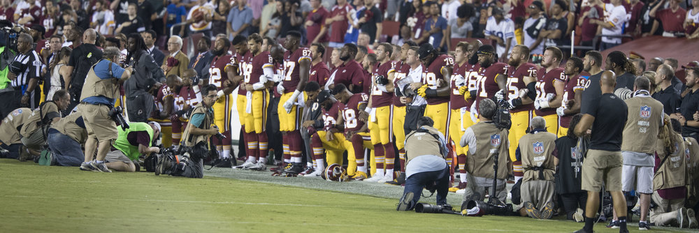 Washington Redskin's players kneeling and standing for the national anthem. Photo by Keith Allison.