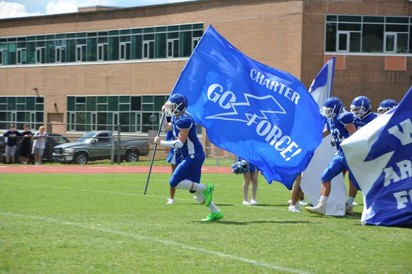 "The Charter football team runs out into the field at a home game this fall, brandishing a ""Go Force!"" banner. Charter's fall sports teams finished off strong this month with several state tournament appearances. Photo from forcessports.com."