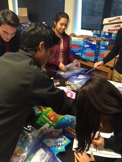 Junior Ben Dubner, sophomore representative Prasanna Krishnamoorthy (reaching), and sophomore Abby Diaz busily assemble kits. Photo courtesy of Henna Castle.