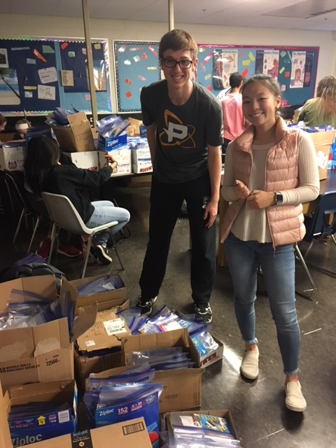 Junior Vice President Mike Mihalow and senior Anna Suh pose for a picture before going back to counting kits. Photo courtesy of Henna Castle.