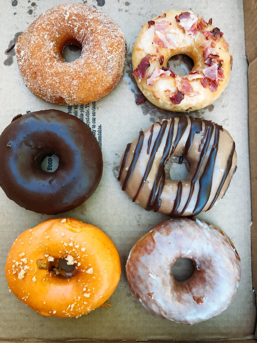 (Left to Right) Cinnamon and Sugar, Maple Bacon, Chocolate Glaze, Chocolate Sea Salt Caramel, Spicy Carrot and Vanilla Glaze