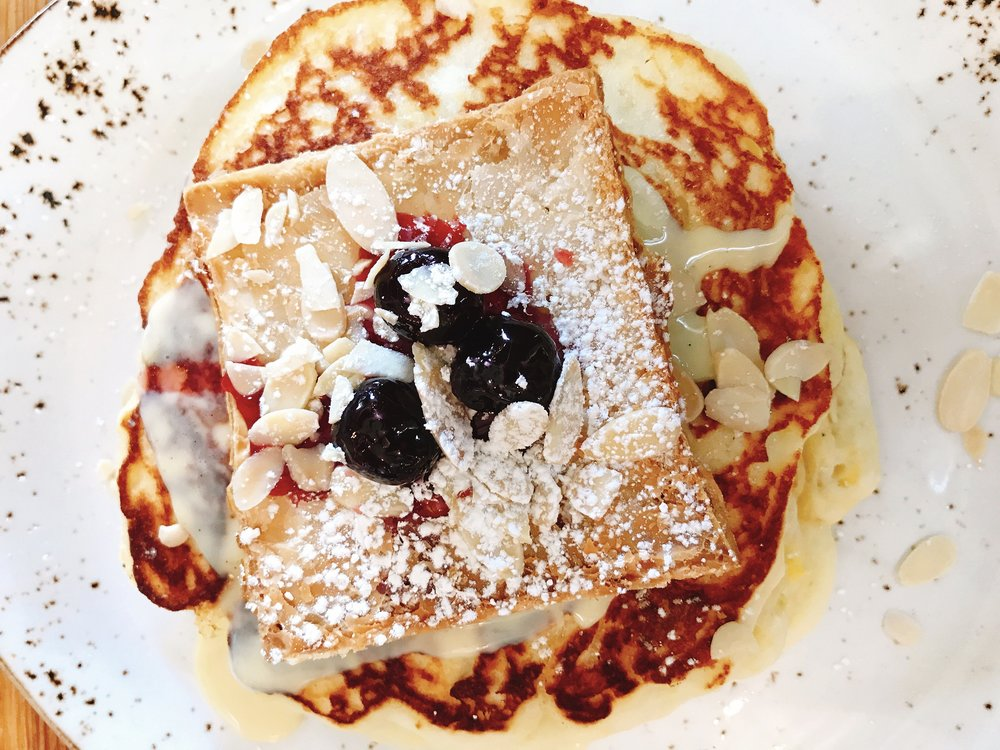 Pancakes served with Fresh Berries, Panna Acida, and Warm Maple Syrup